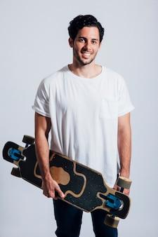 Smiling man holding longboard