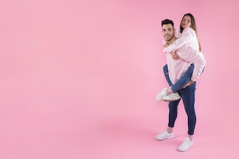 Smiling man holding on back attractivewoman