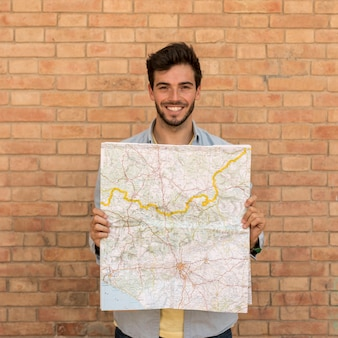 Smiling man holding a open map