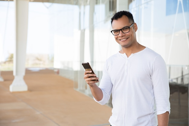 Smiling man holding phone in hands, turning head to camera