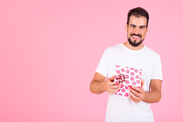 Smiling man holding pink floral gift box against pink backdrop