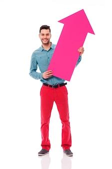 Улыбающийся человек, держащий розовый знак стрелки