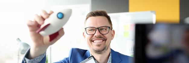 彼の手でロケットとビジネスチャートを持っている笑顔の男は成功を構築するためのルール