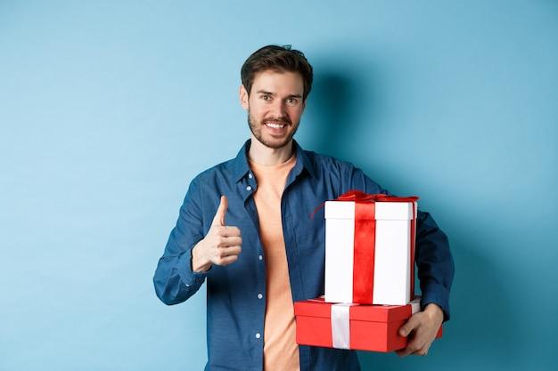 Улыбающийся человек держит романтические подарки и показывает палец вверх, празднует день святого валентина, покупает подарки для любовника, стоя на синем фоне.