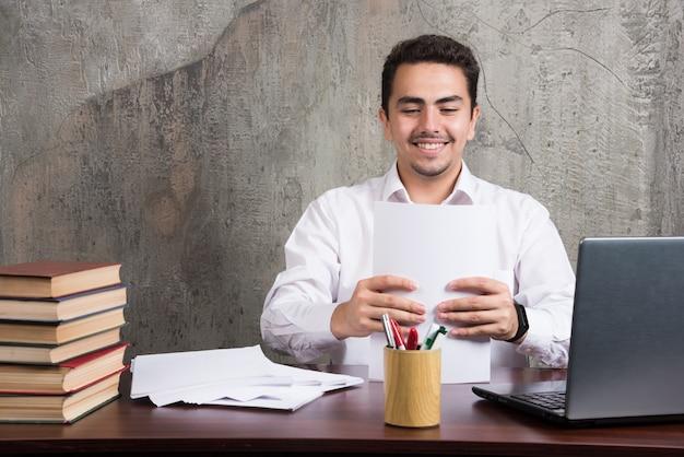 Улыбающийся человек, держащий листы бумаги и сидящий за столом. фото высокого качества