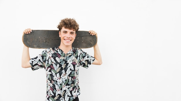 Smiling man holding skateboard on his shoulder against white backdrop