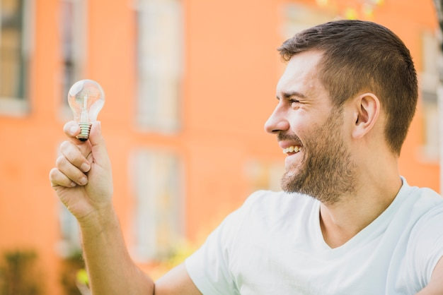Smiling man holding transparent light bulb