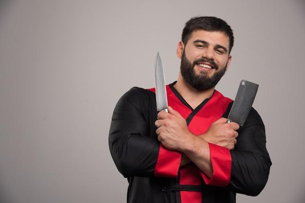 Uomo sorridente che tiene due coltelli sul muro grigio