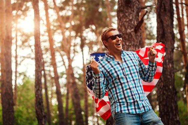 夕暮れ時の公園でアメリカの国旗を持った笑顔の男