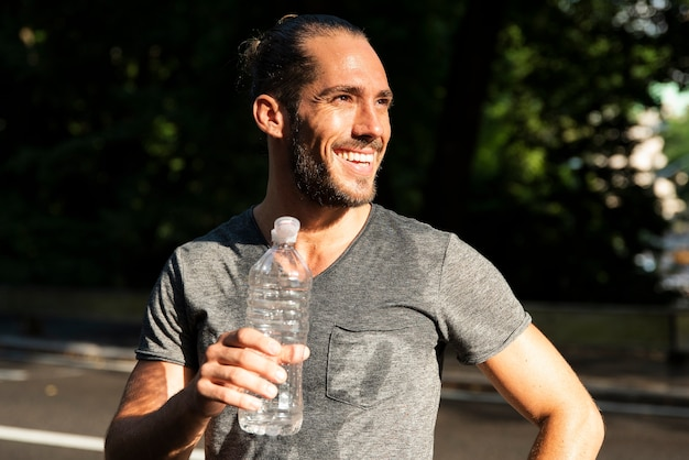 Smiling man holding water bottle