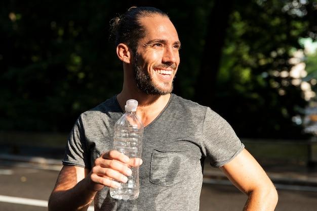 水のボトルを保持している笑みを浮かべて男