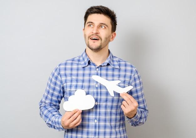Улыбающийся человек держит белую модель самолета и облака