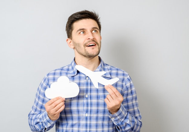 Smiling man holding white paper model of plane and cloud