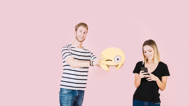 Smiling man holding winking emoji icon near woman with cellphone