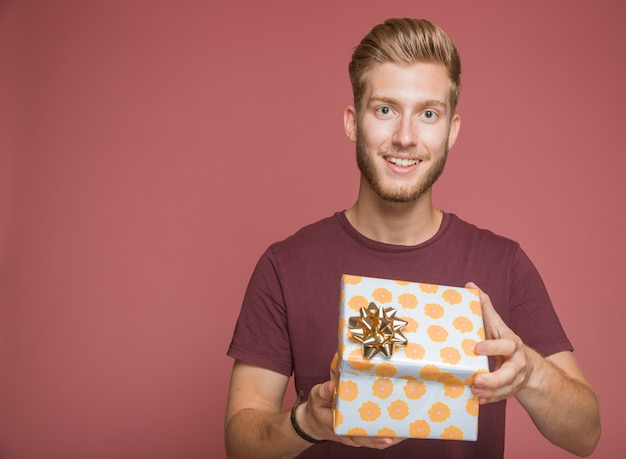 Smiling man holding wrapped gift box against colored background