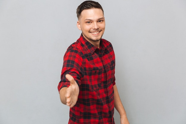 Smiling man holds out his hand for a handshake