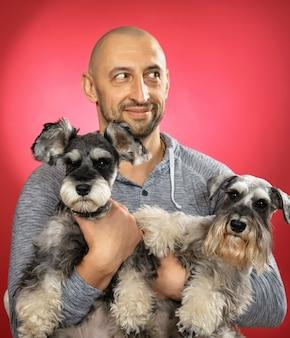 Улыбающийся мужчина держит на руках двух симпатичных собак шнауцера