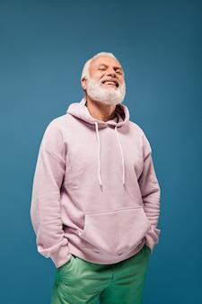 Uomo sorridente in felpa con cappuccio in posa sul muro isolato