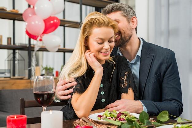 Smiling man hugging cheerful woman at table
