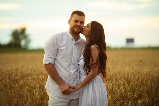 Smiling man hugging her pretty wife while standing behind her on a wheat field during evening sunset. love concept