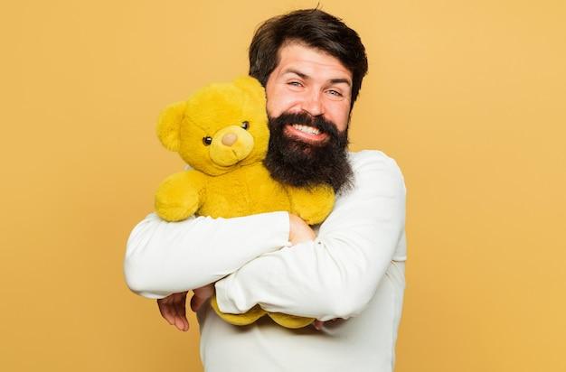 웃는 남자가 테디 베어를 안아줍니다. 선물과 선물. 봉제 장난감을 가진 행복한 남자. 생일 축하.
