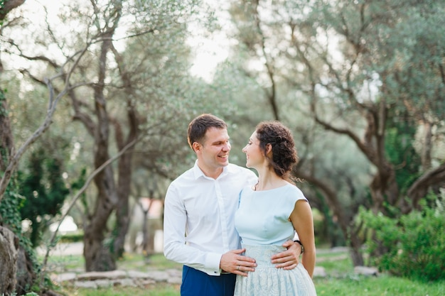 Smiling man hugs womans waist while standing in olive grove between tall trees