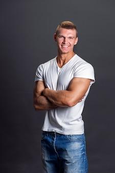 Улыбающийся человек в пустой футболке на серой стене