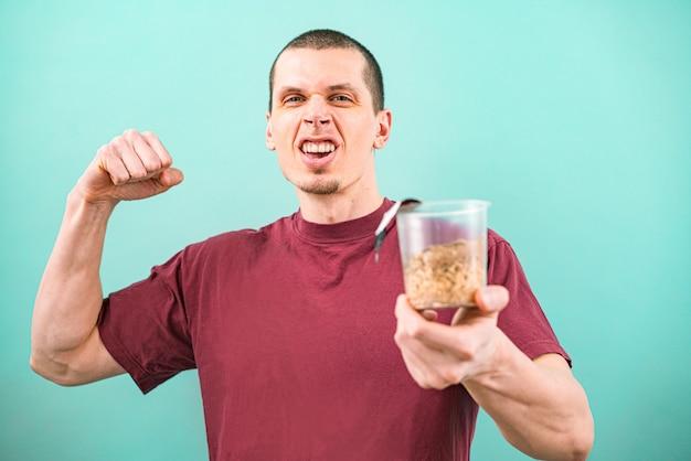부르고뉴 티셔츠에 웃는 남자는 준비되지 않은 패스트 푸드 국수의 투명 컵을 보유하고 밝은 파란색 배경에 팔뚝을 보여줍니다