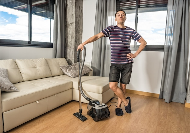 거실을 진공 청소기로 청소하는 캐주얼 옷을 입은 웃는 남자. 전신.