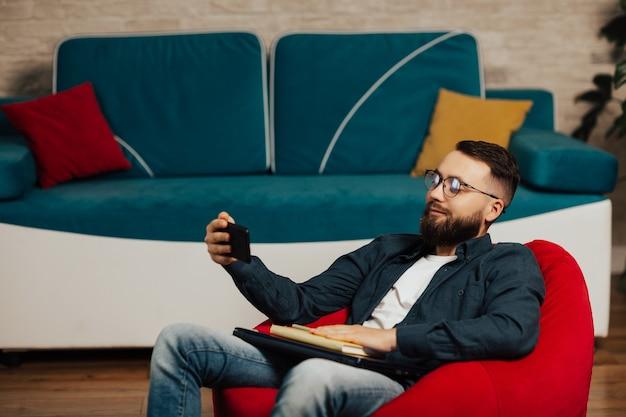 Улыбающийся человек в очках, читая информацию на смартфоне после работы дома на ноутбуке.