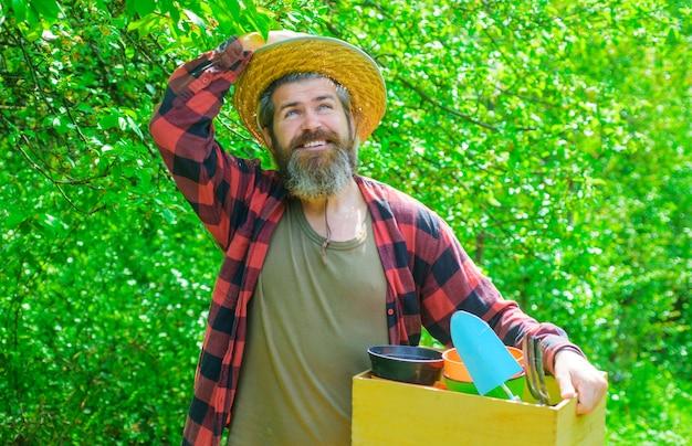 Улыбающийся человек в саду с садовыми инструментами.