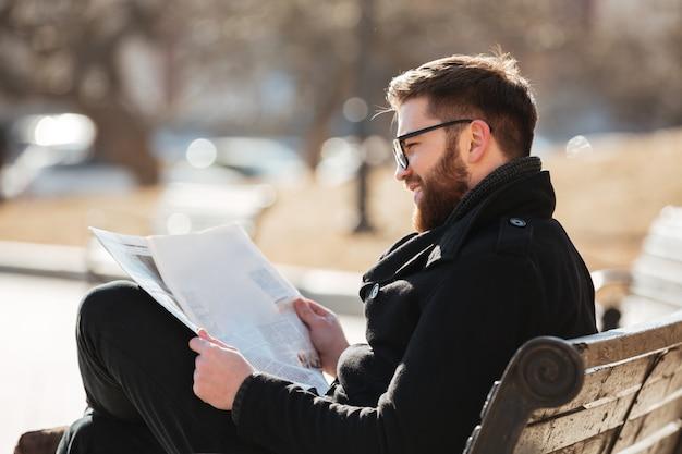 Улыбающийся человек в очках читает газету на скамейке на открытом воздухе