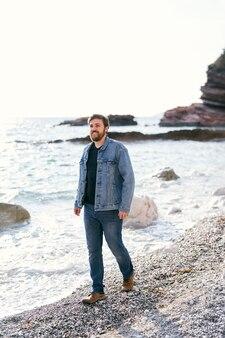 청바지에 웃는 남자와 데님 재킷은 물 근처의 조약돌 해변을 따라 산책합니다.