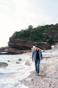 청바지와 데님 재킷에 웃는 남자는 물을보고 조약돌 해변을 따라 걷고