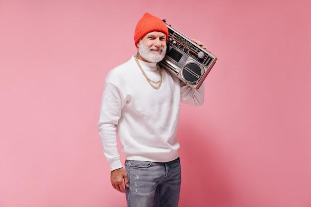 분홍색 벽에 레코드 플레이어와 함께 포즈를 취하는 주황색 모자에 웃는 남자