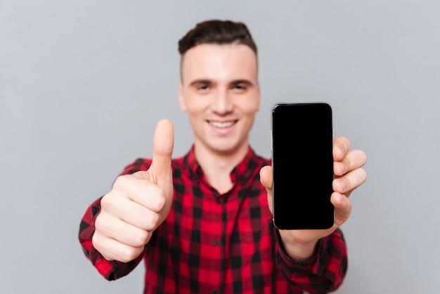 Улыбающийся человек в красной рубашке показывает пустой экран смартфона и показывает палец вверх.