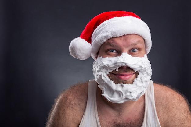 サンタクロースの帽子の男の笑みを浮かべてください。