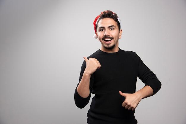 Улыбающийся человек в шляпе санты показывает палец вверх.