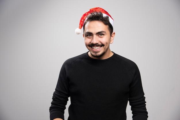 Улыбающийся человек в красной шляпе санты, стоящий над серой стеной.