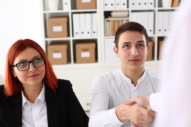 Улыбающийся человек в рубашке пожать друг другу руки в офисе
