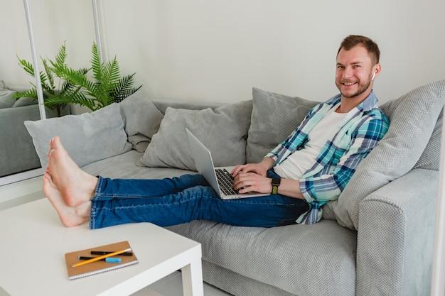 Улыбающийся человек в рубашке расслабленно сидит на диване у себя дома за столом, работая онлайн на ноутбуке из дома