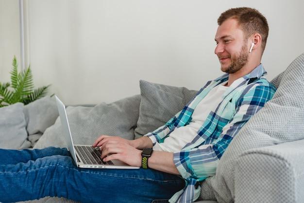 自宅からラップトップでオンラインで作業しているテーブルで自宅のソファでリラックスして座っているシャツの笑顔の男
