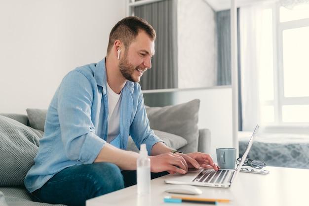 Улыбающийся человек в рубашке расслабленно сидит на диване у себя дома за столом, работая онлайн на ноутбуке