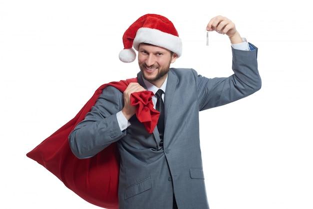 スイートと赤い帽子で笑っている男、肩の上に贈り物と袋を持って、鍵を見せる。