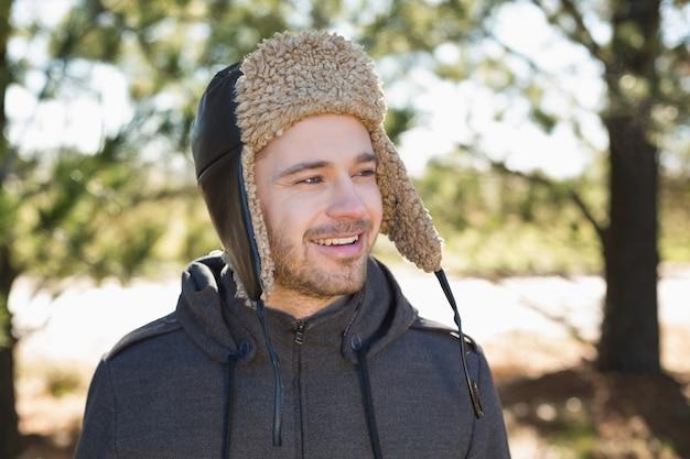 Улыбающийся человек в теплой одежде смотрит на бок в лесу