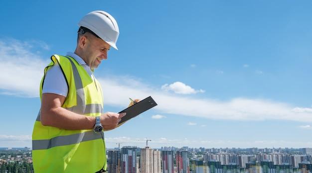 건설 현장에서 흰색 헬멧을 쓴 웃는 남자가 클립보드에 메모를 씁니다.