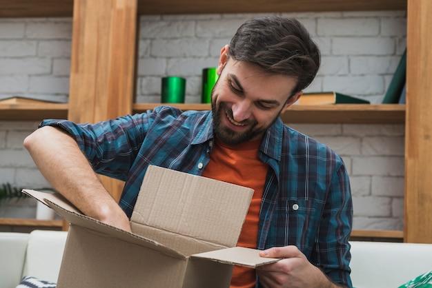 Uomo sorridente che ispeziona il pacchetto