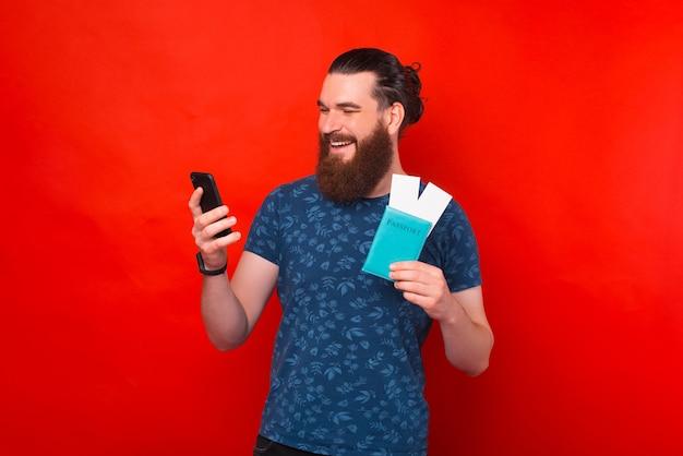 Улыбающийся человек проверяет телефон, держа в руках паспорт с билетами.