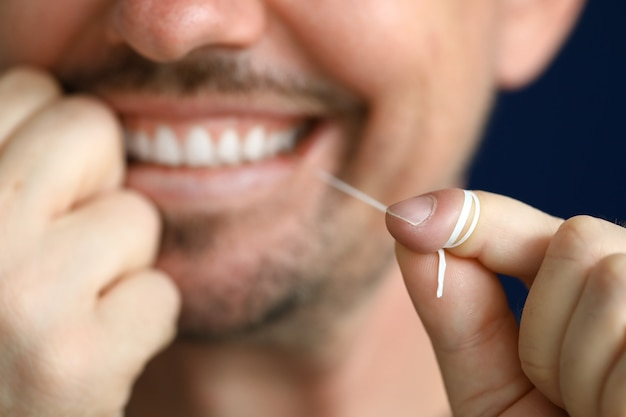 Smiling man is cleaning interdental space with dental floss.