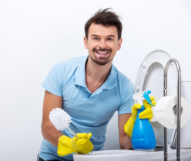 Smiling man is cleaning toilet with spray cleaner and brush.